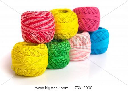 Multicolored skeins of yarn are laid out in a double row.
