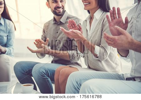 Business people are applauding and smiling while sitting in circle in office