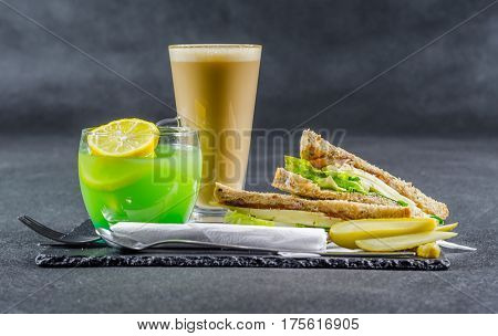 set consisting of two sandwiches malted bread with vintage cheddar cheese pickles red onion tomato lettuce green drink and coffee latte breakfast set