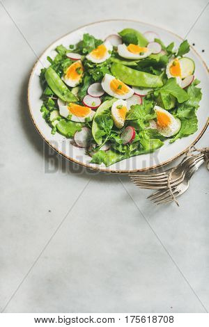 Healthy spring green salad with radish, boiled egg, arugula, green pea and mint in white plate over grey marble background, selective focus, copy space, vertical composition