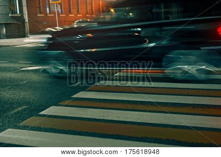 Crosswalk in city with fast moving blurred car at night. Pedestrian safety concept.