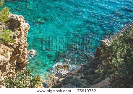 Stairs over rock and way down to lagoon and turquoise sea waters at South Mediterranean coast of Turkey near Koru beach in Gazipasa town