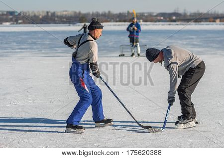 Dnepr Ukraine - January 22, 2017: Mature man fighting for the pack while playing hockey on a frozen river Dnepr in Ukraine