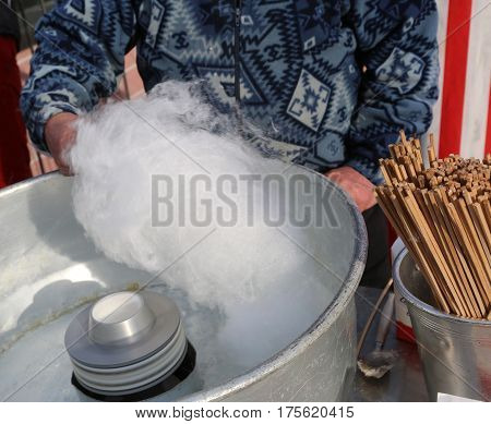 man make cotton candy in the funfair for the children