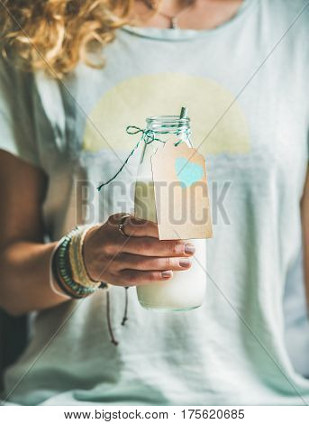 Young blond woman in light t-shirt holding bottle of dairy-free almond milk in her hand. Clean eating, vegan, vegetarian, dieting, healthy food concept