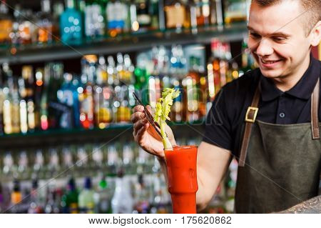 The bartender making cocktail Bloody Mary in a nightclub bar. Decorate with celery.