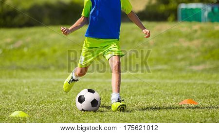 Young Soccer Player Kicking Ball on Soccer Pitch. Boy in Sports Clothing Playing Football. Child Training Soccer with Soccer Equipment