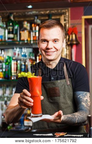 The bartender presents cocktail Bloody Mary to the client.