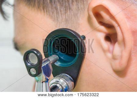 otoscope looking left ear man patient concept healthcare