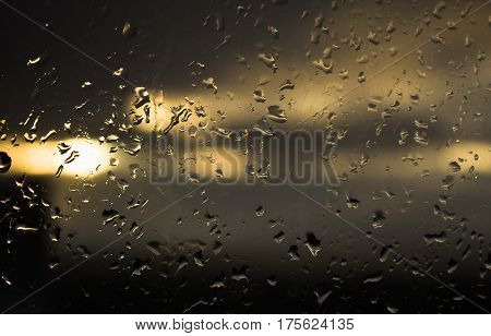 Drops of rain on a window in the sunset