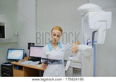 Dentist Analyzes A Dental Panoramic X-ray Film