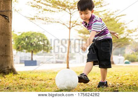 Boy kick ball at the park in the evening.