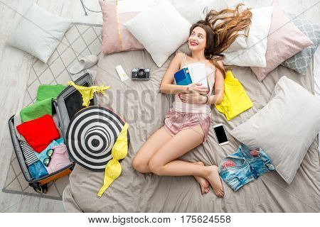 Top view on the bed with young woman, different clothes and stuff for summer vacations. Dreaming about summer trip concept
