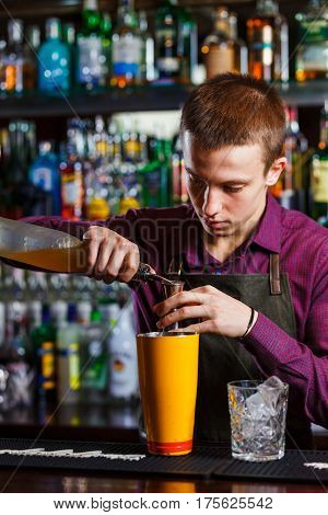 The bartender making cocktail in a nightclub bar. Pouring liquor.