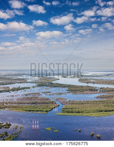View from above of flooded forest plains with power lines.