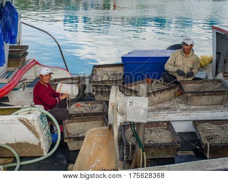 Fuji Taiwan - October 03 2016: Taiwanese fishermen on the boat curling fishing nets