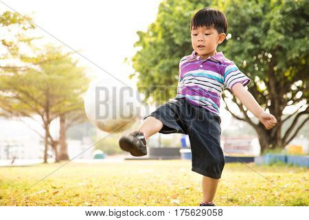 Boy learning kick ball at the park in the evening.