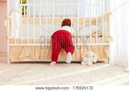 Cute Toddler Baby Climbing Into The Cot In Nursery Room At Home
