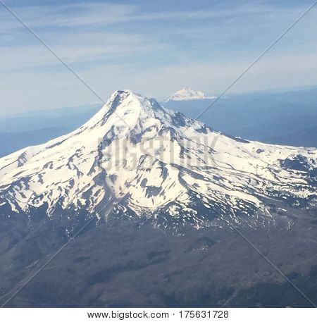 Volcanic cone shaped snow covered mountain looms outside plane window..
