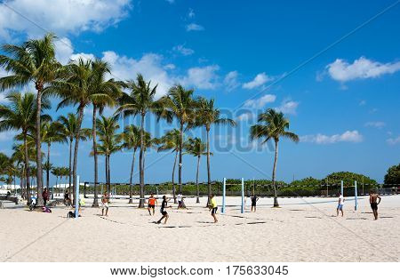 MIAMI BEACH FLORIDA - FEBRUARY 15 2017: Group of men play a friendly game of volleyball on the sands of Miami Beach Florida USA on February 15 2017.