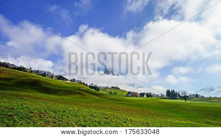 Alpine Natural Landscape With Green Fields, High Rocks And White Clouds