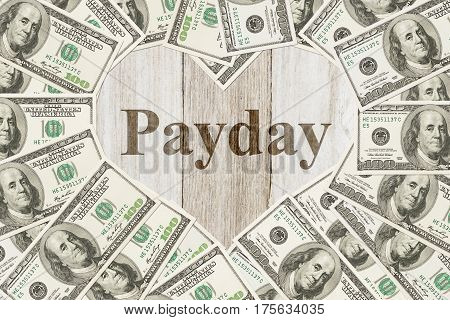 The love payday message One hundred dollar bill in the shape of a heart with a weathered wood heart with text Payday