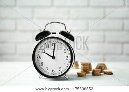 Alarm clock and coins on white table against brick wall background