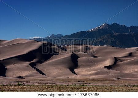 Contrast between the solid rock mountains and the drifting sands in the Great Sand Dunes National Park in southern Colorado near Alamosa