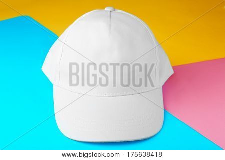 Blank white baseball cap on color paper background