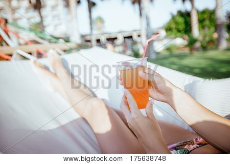 woman holding green cocktail in the hammock at the beach