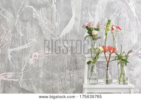 Beautiful flowers in glass vases on step ladder against textured wall background