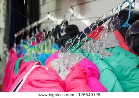 Beautiful warm colorful jackets hang on hangers inside the clothing store. Beautiful clothes for the winter autumn season. Classic Design Store Products