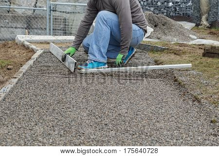 Worker leveling a metal screed board to gravel surface