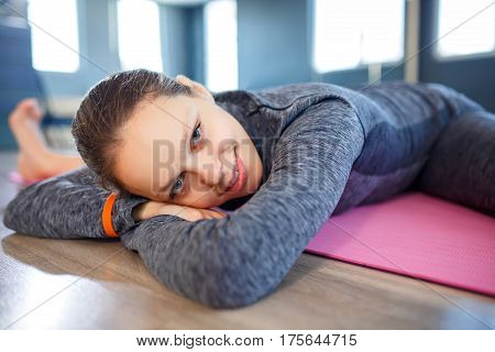 Young woman relaxing in gym lying on pink yoga mat concept healthy lifestyle, training, diet. Portrait of smiling sport's woman. Healthy lifestyle. Closeup.