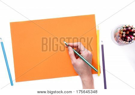 Female hand is ready for drawing with green pencil on orange paper. Isolated on white. Concept. Art and design. Drawing and painting. Hobbi.