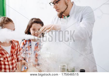 Interaction of chemical reagents. Serious nice experienced scientist performing an experiment and being surrounded by smoke while having an optional chemistry lesson