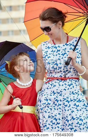 Mother and daughter stand together holding rainbow coloured umbrellas.