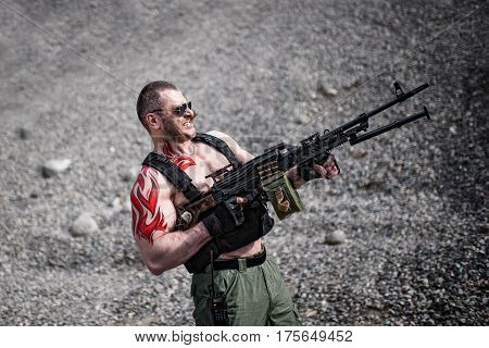 Strong soldier with a machine gun and a cigar