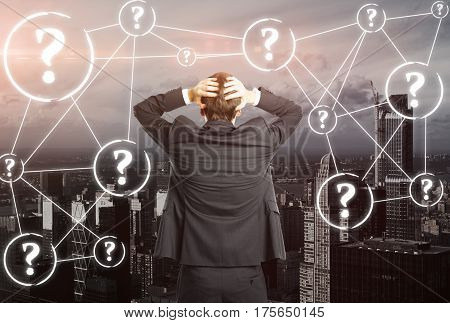 Back view of worried businessman on city background with connected question marks. FAQ concept