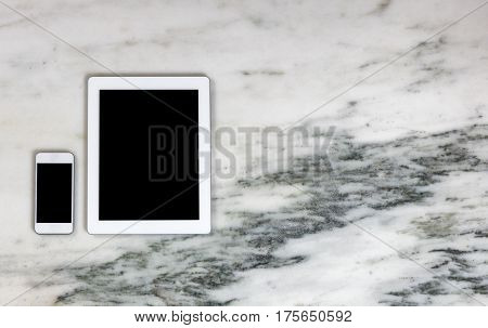 Overhead view of modern wireless mobile communication devices on marble desktop. Paperless office concept.