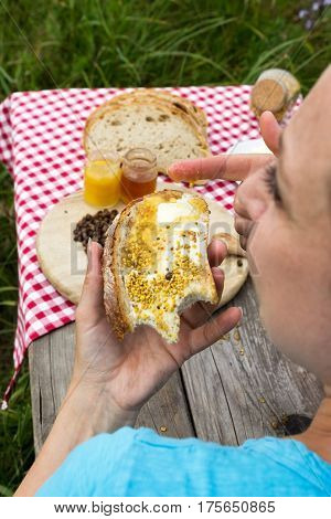 Woman eating a sandwich with honey outdoors
