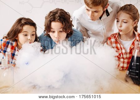 Smart kids. Curious positive clever children standing together and leaning forward while blowing on the chemical fume
