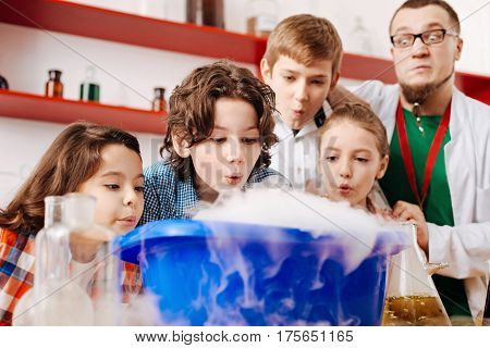Successful experiment. Enthusiastic pleasant positive children standing around the washbowl and blowing on it while focusing on the activity