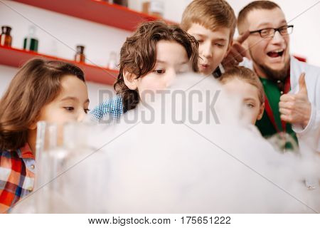 Everything is perfect. Happy positive nice teacher showing thumbs up sign and smiling while standing behind children