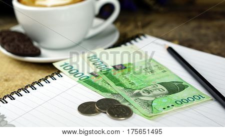 Korean Won and a cup of coffee. Currency foreign exchange. Business and Financial or money management for investments.