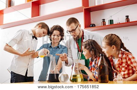 Childish enthusiasm. Exited happy smart children carrying out n experiment and being focused on it while having a science lesson