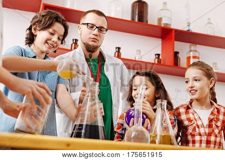 Science lovers. Positive delighted intelligent children standing around the table and conducting an experiment while attending a scientific club meeting