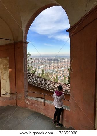 BOLOGNA - MARCH 7, 2017: A woman enjoys the scenic city view from a window on the Portico di San Luca connecting Porta Saragozza with the San Luca Sanctuary, on Colle della Guardia in Bologna, Italy.