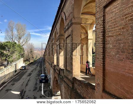 BOLOGNA - MARCH 7, 2017: A pedestrian walks downhill along the Portico di San Luca connecting Porta Saragozza with the San Luca Sanctuary, on Colle della Guardia in Bologna, Italy.