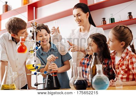Interesting lesson. Cheerful positive cute children standing around the teacher and being involved in the lesson while enjoying chemistry experiments